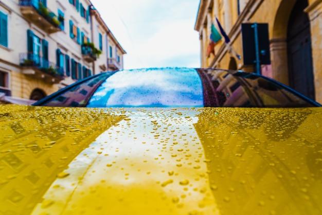 Капли дождя на гладкой блестящей поверхности капота припаркованной в городе новой машины.