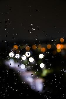 窓ガラスと常夜灯のボケ味の背景に雨滴。ぼやけたライト。抽象的な雨の背景