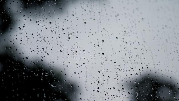 Текстура капель дождя на стеклянной оконной раме комнаты кафе и природы