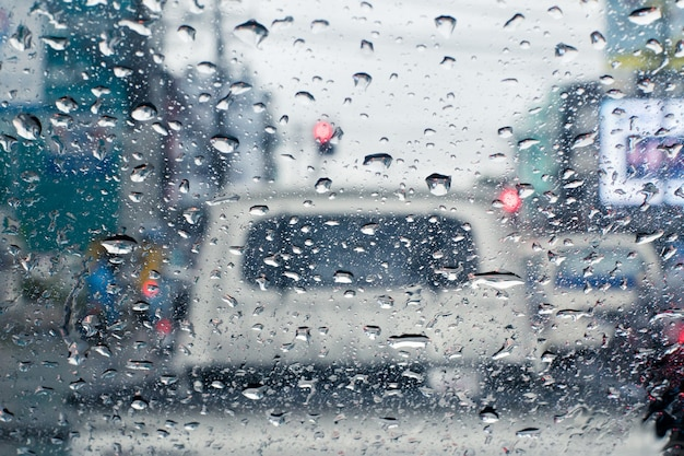 Raindrops on windshield from inside the car in traffic jam
