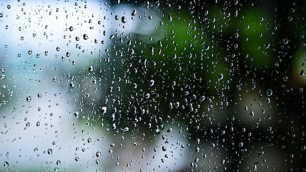 Дождь падает на стекло окна с природой бохе