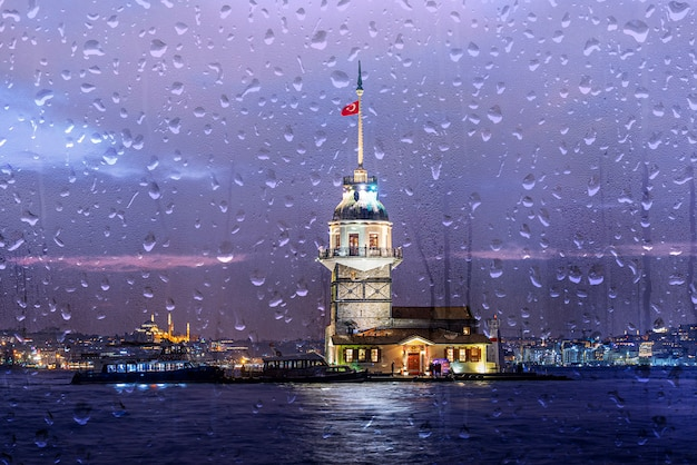 Raining evening in istanbul, maiden's tower or kiz kulesi in night time in istanbul, turkey