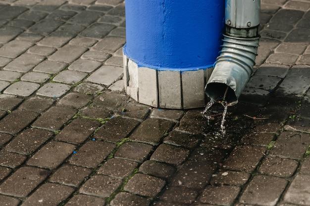 雨水が排水管から流れ出る