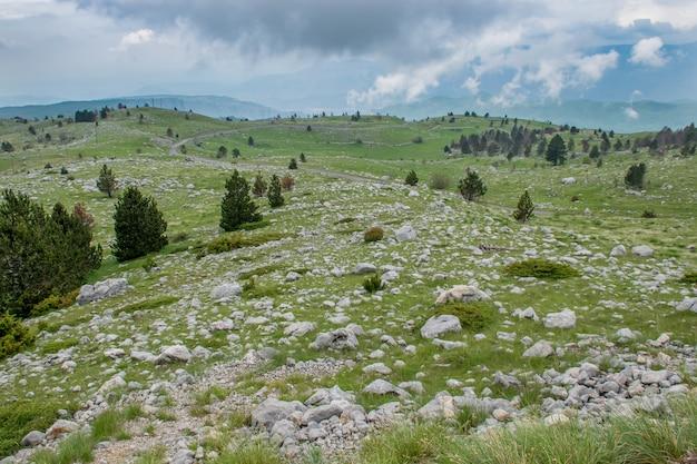 雨の雲が緑の山の牧草地に近づいています。