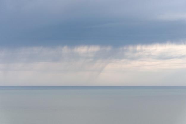 Rainy clouds over a calm sea,  strip of rain on horizon, soft focus, long exposure, abstract seascape.