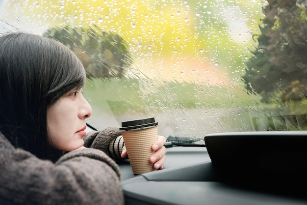 Rainy day or bad weather in a vacation concept. a sadness woman waiting for rain to stop