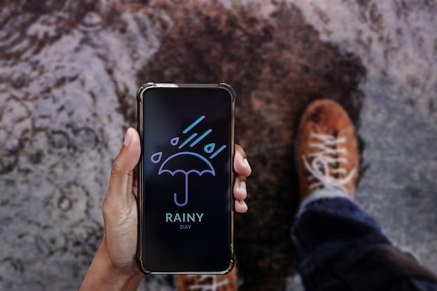 비오는 날 개념. 보도에서 우산을 들고 걷고 휴대 전화를 통해 일기 예보를 보는 남성