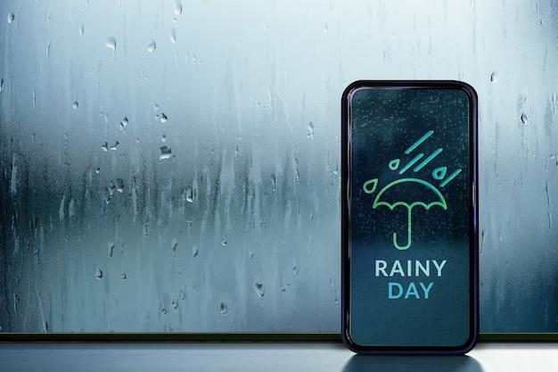 비오는 날 개념. 휴대 전화 화면에 날씨 정보 예보를 보여줍니다. 유리창을 통해 내부에서보기