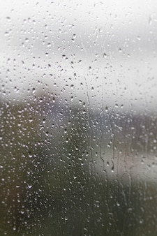 Дождливый день через окно на фоне пасмурного серого неба и городских зданий. концепция. вечерний городской пейзаж за стеклянным окном с каплями воды.