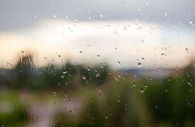 曇り灰色の空と都市の建物の背景の窓から雨の日。概念。ガラス窓の後ろの夜の街並みと水滴が滴り落ちる。