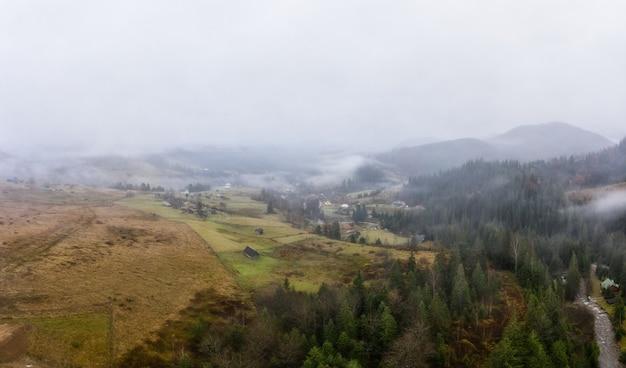 Дождливая туманная и серая погода в горной долине карпат на украине в небольшой деревне панорамный снимок с дронов с воздуха