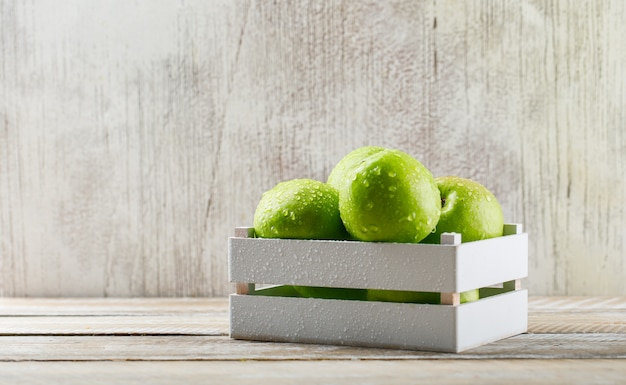 Rainy green apples in a wooden box on grunge and light wooden background.