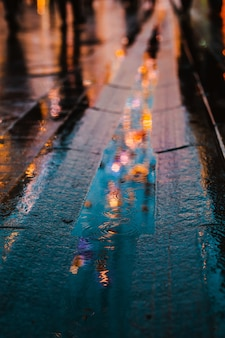 Rainy night in a big city, reflections of lights on the wet road surface.