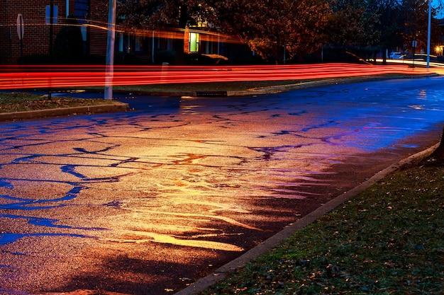 Дождливая ночь в большом городе, свет из витрин магазинов отражается на дороге, по которой едут машины. вид с уровня асфальта