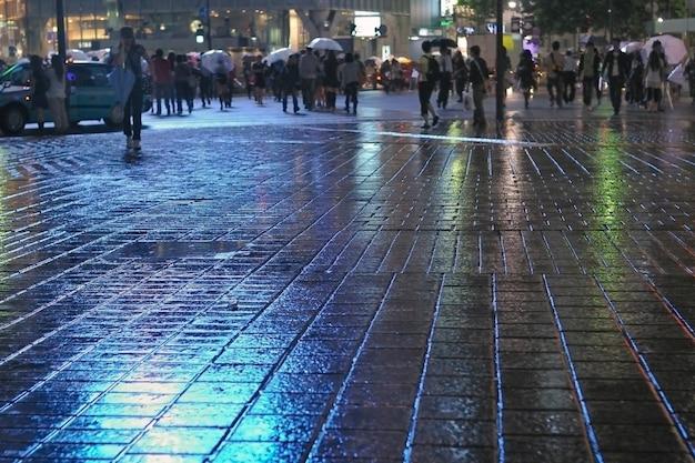 Отражение дождя на тротуаре ночью с толпой в токийском мегаполисе, фокус на тротуаре
