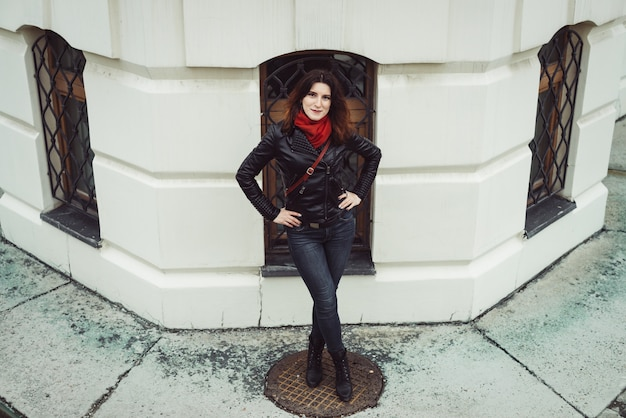 Rainy portrait of beautiful pensive girl with curly brown hair in black leather jacket, blue jeans, red scarf and red handbag