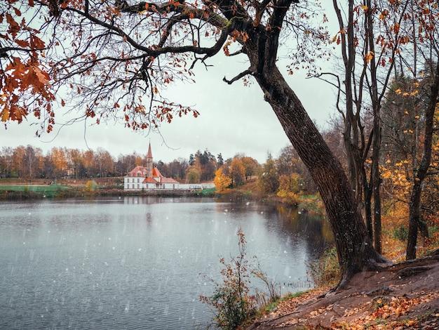 Дождливый снежный осенний пейзаж с деревом на берегу озера и старым замком на расстоянии. россия.