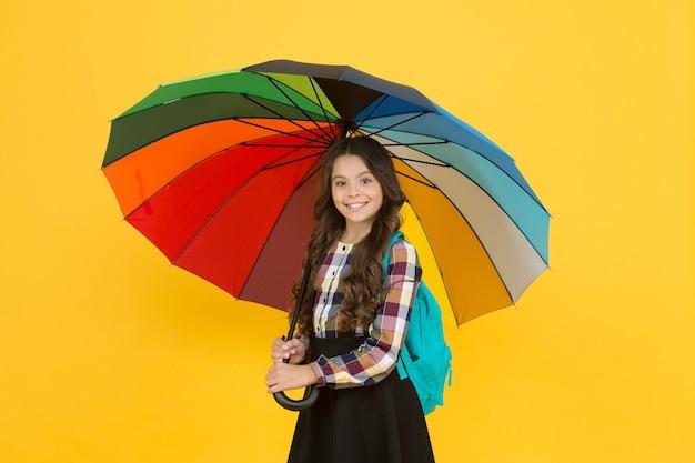 Rainy weather with proper garments. on way to school. cheerful smiling schoolgirl. rainy day fun. happy walk under umbrella. enjoy rain concept. kid girl happy hold colorful rainbow umbrella.