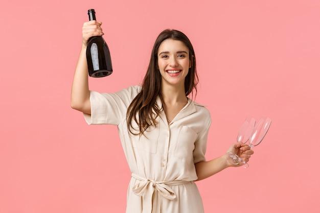 Поднимите свои очки, дамы. беззаботная счастливая молодая женщина празднует девичник, держит бутылку шампанского и бокал, улыбается, подбадривает, веселится, развлекается на розовой стене