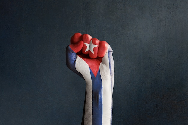 Raised fist with cuban flag on a dark textured background