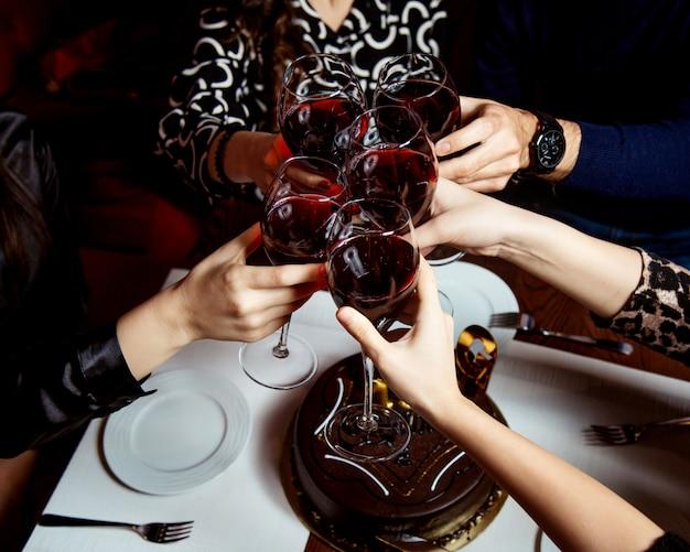 Поднятые бокалы красного вина и шоколадный торт