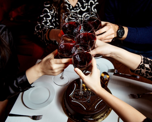 Raised glasses of red wine and chocolate cake