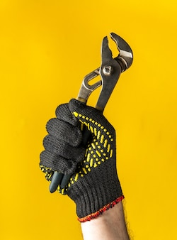 Raised hand in construction glove of a master plumber holds a pliers