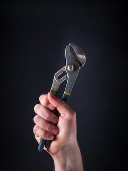 Raised hand of a master plumber holds pliers
