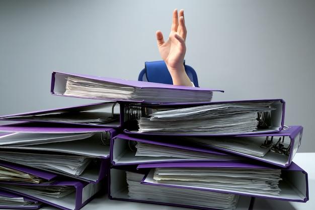 Поднятые руки человека, который тонет за стопками папок на офисном столе. понятие чрезмерных требований и увеличения работы в бизнесе