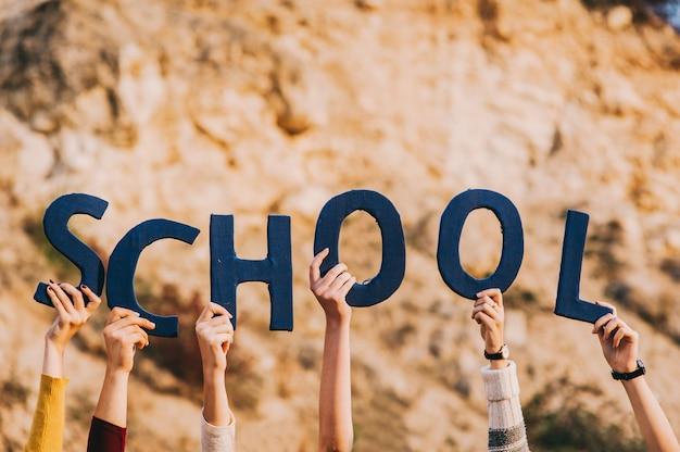 Поднятые руки безликих мальчиков и девочек держат синие буквы