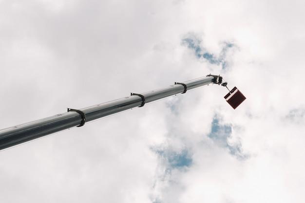 Высоко в небе поднятый люлькой автомобильного крана. самый высокий автокран с желтой люлькой для решения сложных задач.