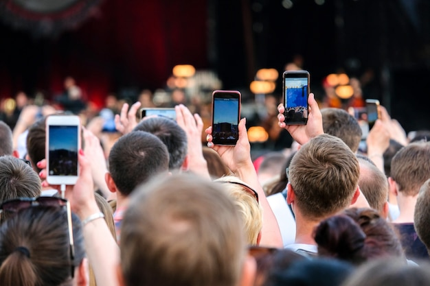 Raised outstretched hands with smartphones photographing stage in the crowd during a concert.