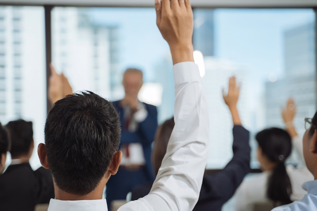 Raised up hands and arms of large group in seminar