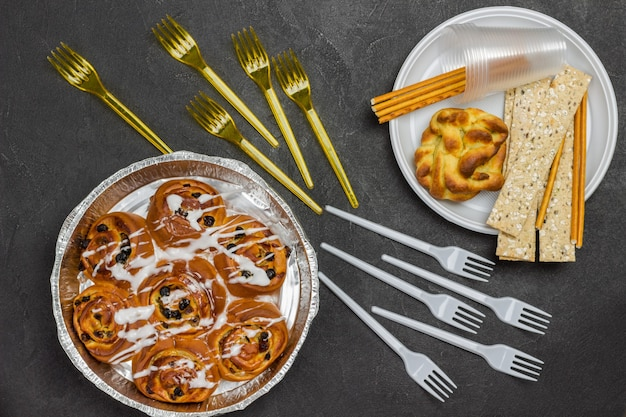 Булочки с изюмом в форме для выпечки. булочка и хрустящие хлебцы в пластиковой одноразовой тарелке.