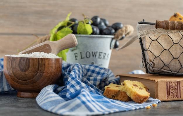 大理石のテーブルにレーズンケーキ、ブドウ、小麦粉