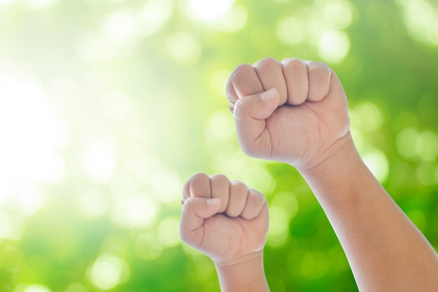 Raising hands on green natural bokeh blurred abstract background