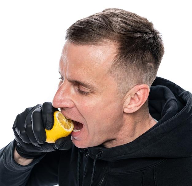 면역 및 건강 관리 개념을 높입니다. 흰색 바탕에 레몬을 물어뜯는 남성