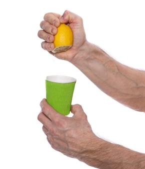 免疫力とヘルスケアの概念を高める。レモンの半分を白い背景の上のガラスに絞る男性