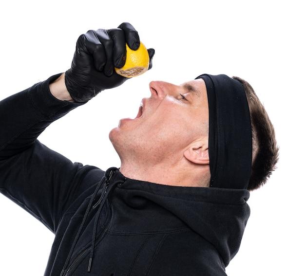 면역 및 건강 관리 개념을 높입니다. 흰색 바탕에 입에 레몬 반을 짜내는 남성