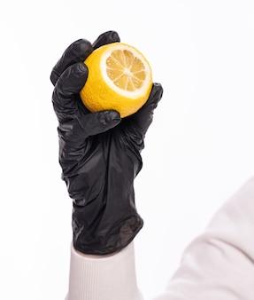 면역 및 건강 관리 개념을 높입니다. 흰색 배경 위에 레몬을 들고 보호 장갑을 끼고 있는 여자