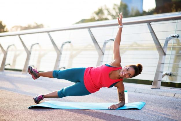Подъем ноги. женщина поднимает ногу, делая боковую планку на улице утром
