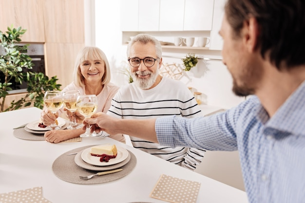 両親のためにグラスを上げる。カリスマ的な喜びのハンサムな男は、シャンパンと挨拶でいっぱいのグラスを上げながら、夕食を食べ、彼の年配の両親と一緒に休日を楽しんでいます