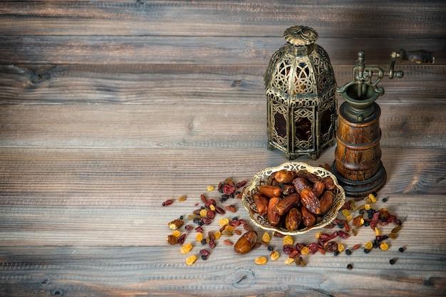 나무 배경에 건포도와 날짜입니다. 빈티지 오리엔탈 랜턴과 밀이 있는 아랍어. 음식 개념입니다. 레트로 톤의 사진