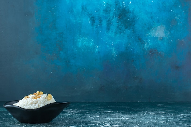 Raisins on a bowl of rice pudding , on the blue background. high quality photo