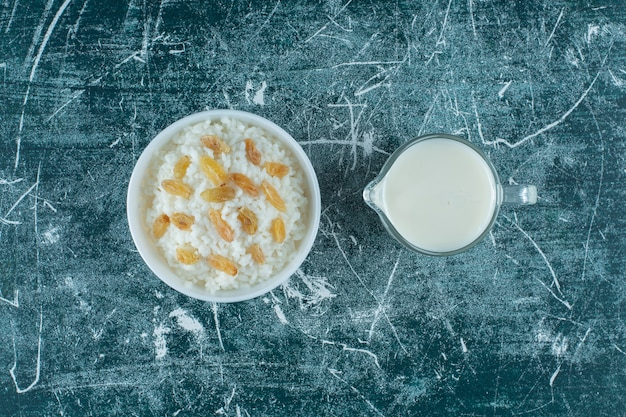Raisins on a bowl of rice pudding next to a glass of milk, on the blue table.