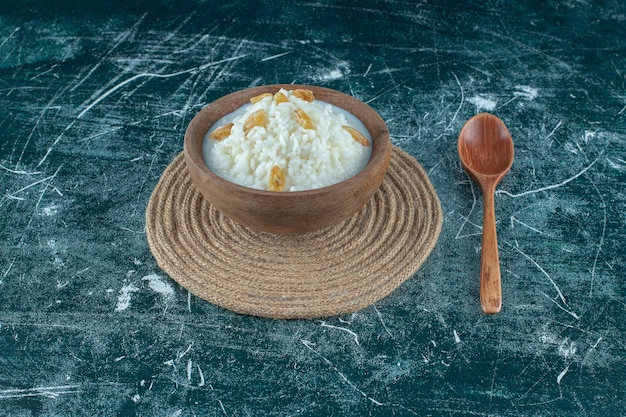 Raisins on a bowl of rice pudding next to spoon , on the blue background. high quality photo