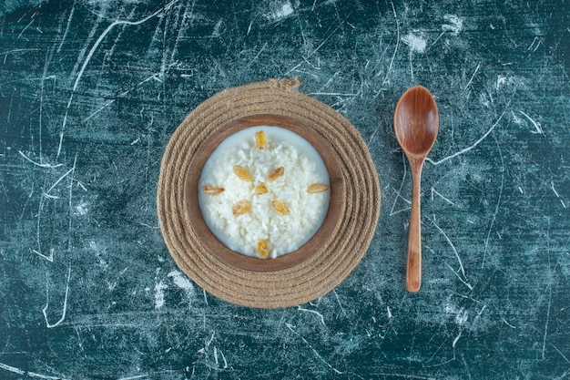 Uvetta su una ciotola di budino di riso accanto al cucchiaio, sul tavolo blu.