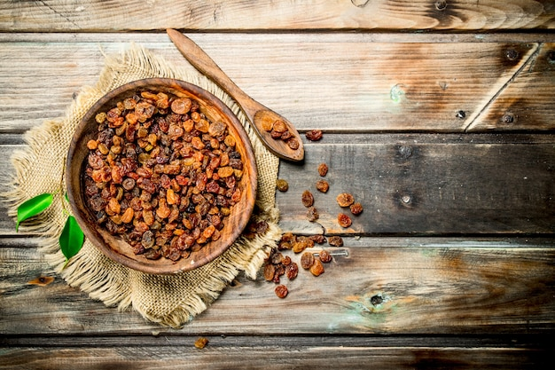 Raisins in bowl on rustic table.