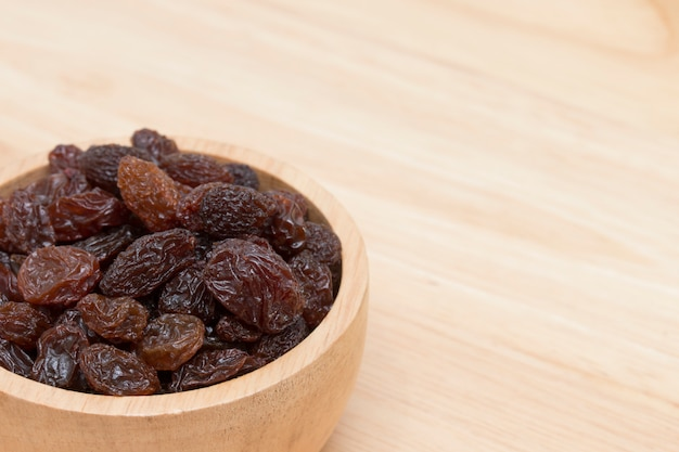 Raisins in bowl on wooden table.