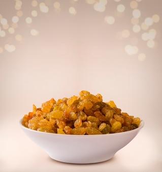 Raisins into a bowl on beige background.